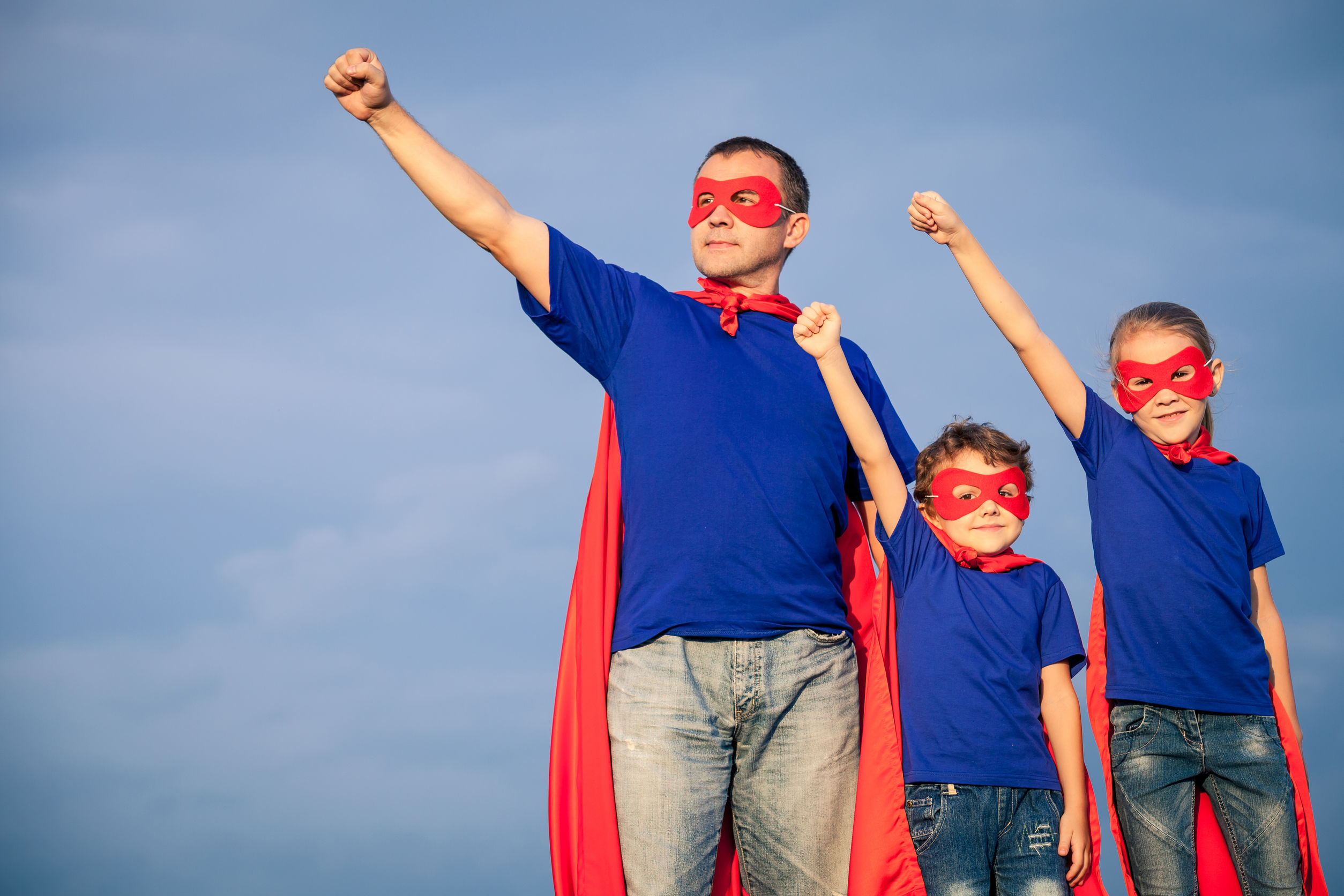 Stock Photo - Father and children playing superhero at the day time. People having fun outdoors. Concept of friendly family.