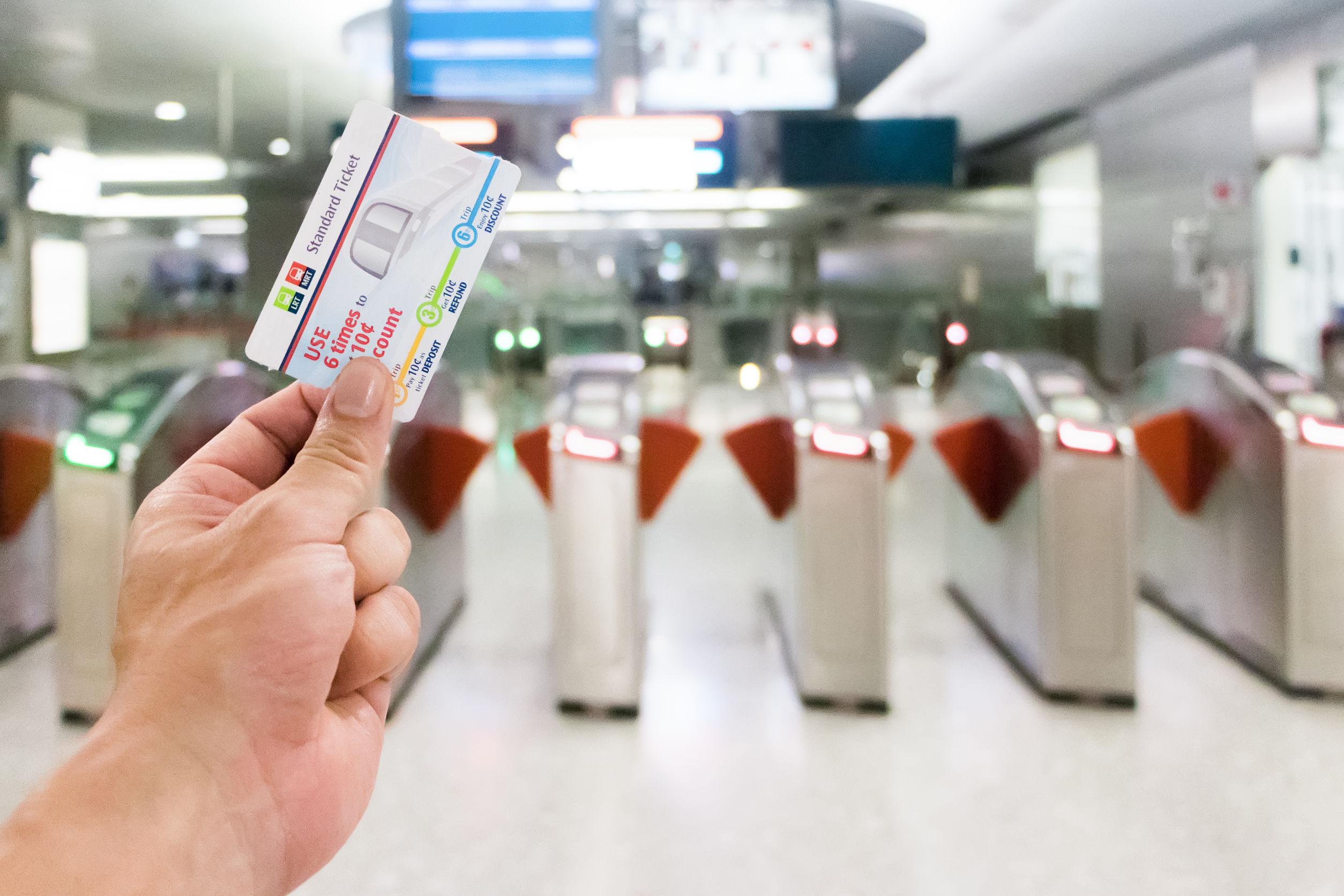Stock Photo - 25-February 2018 Passenger holding ticket at the entrance at Singapore MRT station